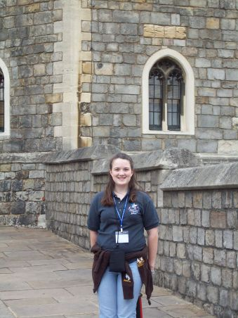 Chelsea smiling in front of Windsor Castle wearing a gray polo.